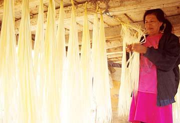 A weaver hangs straw under her house to dry.