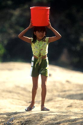 Girl carries bucket of water on her head.